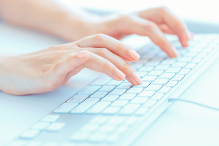 peripherals: Female hands or woman office worker typing on the keyboard