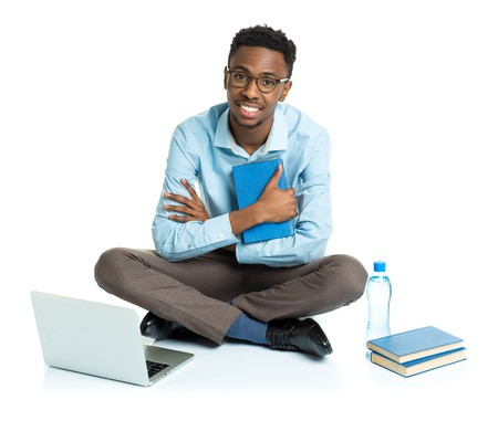 computer isolated: Happy african american college student with laptop, books and bottle of water sitting on white background