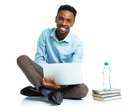 college: Happy african american college student with laptop, books and bottle of water sitting on white background
