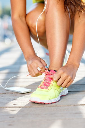 jogging shoes: Running shoes - woman tying shoe laces. Closeup of female sport fitness runner getting ready for jogging outdoors on waterfront in late summer or fall