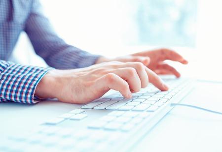 laptop keyboard: Male hands or men office worker typing on the keyboard Stock Photo