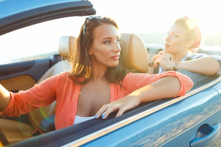 car driving: Two young happy girls driving a cabriolet Stock Photo
