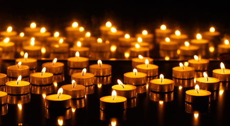 symbols of peace: Panorama of the many burning candles with reflection in the mirror Stock Photo