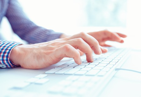 information technology: Male hands or men office worker typing on the keyboard Stock Photo