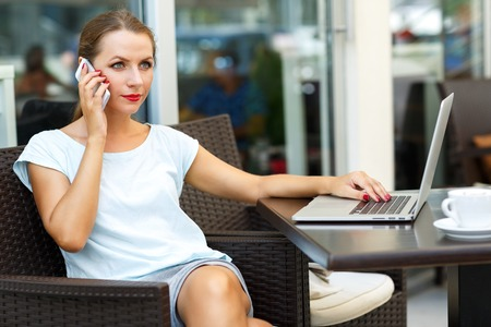 Attractive young woman sitting in a cafe with a laptop and talking on the cell phone Stock Photo