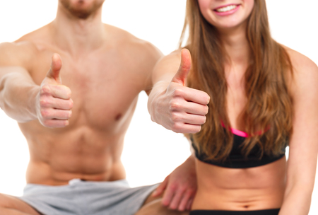 fit couple: Sport man and woman after fitness exercise with a thumb up on the white background