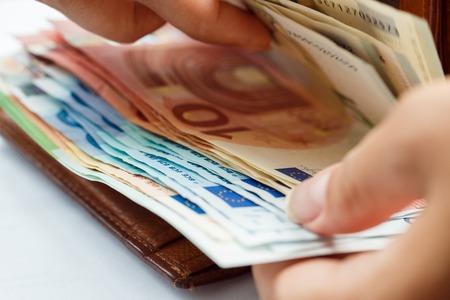 ユーロ紙幣の茶色の革財布を開く女