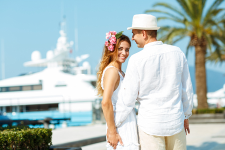 citytrip: Attractive young couple walking alongside the marina with moored boats on a luxury waterfront in summer sunshine - wedding concept Stock Photo