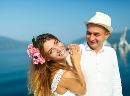 citytrip: Attractive young couple walking alongside the marina on a luxury waterfront in summer sunshine - weedding concept