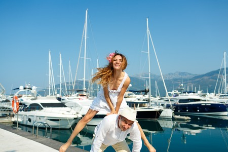 citytrip: Attractive young couple have fun in the marina with moored boats on a luxury waterfront in summer sunshine - wedding concept