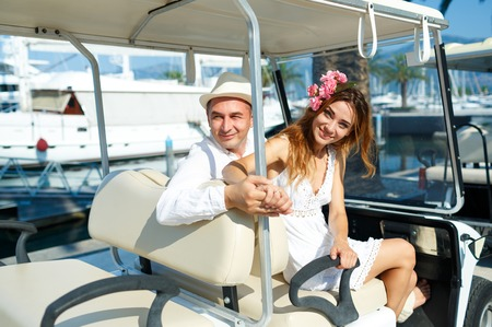 citytrip: Attractive young couple driving electric car on the marina on a luxury waterfront