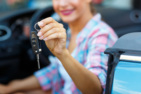 sports cars: Young pretty woman sitting in a convertible car with the keys in hand - concept of buying a used car or a rental car