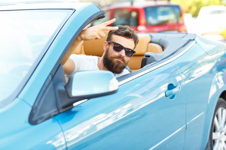 コンバーチブル - 中古車やレンタカーで買うという考えに座っている若いアゴヒゲ 写真素材