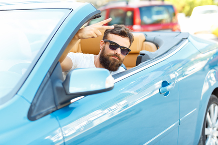 A young bearded man sitting in a convertible -  - the concept of buying a used car or a rental car