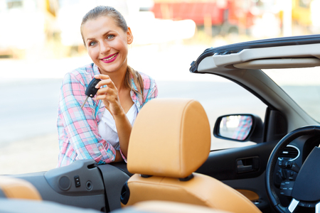 rental: Young woman standing near a convertible with keys in hand - concept of buying a used car or a rental car