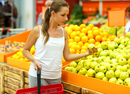 supermarket: Young beautiful woman shopping in a supermarket in the department of fruit and vegetables Stock Photo