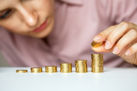 pile of coins: business woman stacking gold coins into increasing columns