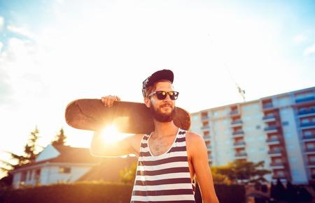 sunglasses: Hombre con estilo joven en gafas de sol con una patineta en una calle de la ciudad a la luz del atardecer