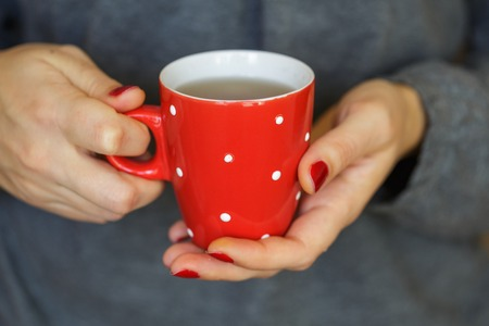 red hand: Woman hands holding a cozy red mug. Stock Photo