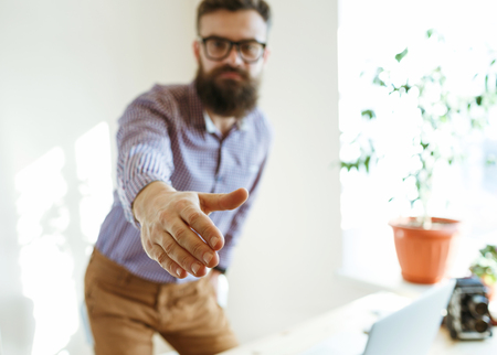 arm extended: Beard business man with arm extended to handshake Stock Photo