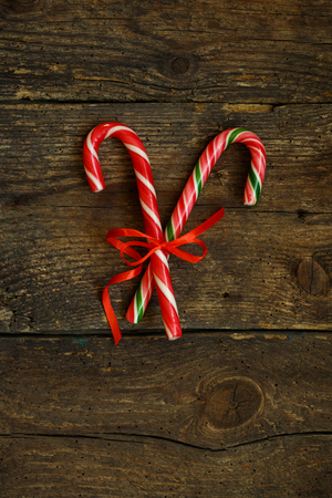 Closeup of two old fashioned candy canes on a rustic wooden background. The treats are crossed and tied with a red ribbon Stock Photo
