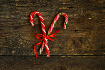 minty: Closeup of two old fashioned candy canes on a rustic wooden background. The treats are crossed and tied with a red ribbon Stock Photo