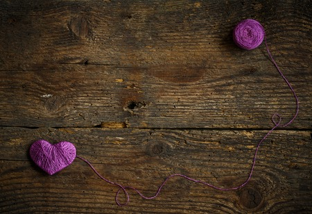 descriptive colour: Purple Heart with a ball of thread on on old shabby wooden background. Image of Valentines day