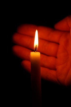 protects: Hand protects the flame of a burning candle on a black background