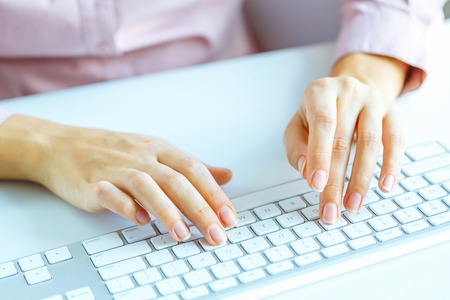 inputting: Female hands or woman office worker typing on the keyboard