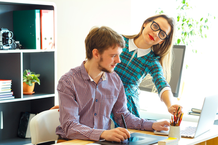 telecommuting: Beautiful young woman and man working from home - modern business concept