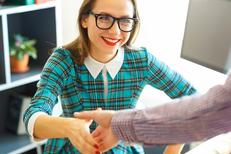 pacto: Modern young  business woman with arm extended to handshake Foto de archivo