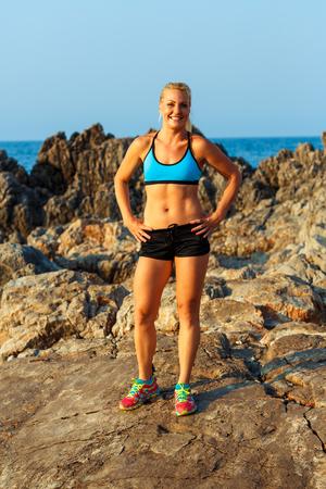 Belle athlète femme, debout, après le sport exercice sur les rochers en bord de mer