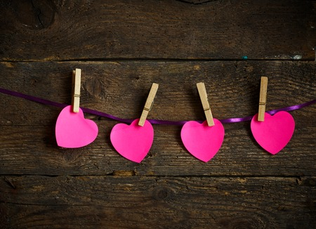 clothes pins: Pink heart paper cut out with clothes pins. Image of Valentines day season