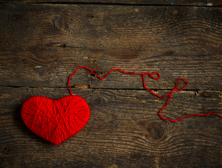 descriptive colours: Red heart shape made from wool on old shabby wooden background. Image of Valentines day