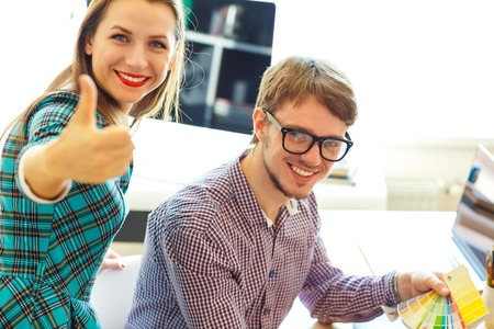 telecommuting: Beautiful young woman and man with thumb up in office - modern business concept