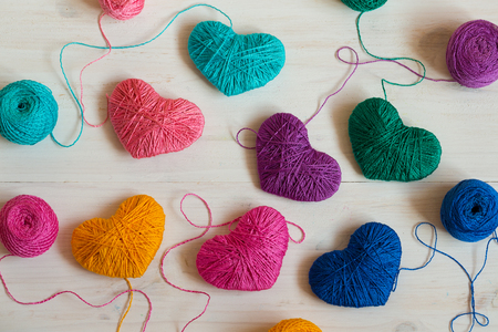 descriptive colours: Multicolored Hearts with a balls of thread on white wooden background. Image of Valentines day