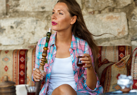 turkish ethnicity: Beautiful young woman smoking a hookah and drinking tea in a cafe, Istanbul, Turkey Stock Photo