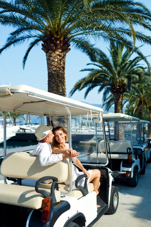 adult couple: Attractive young couple driving electric car on the marina on a luxury waterfront