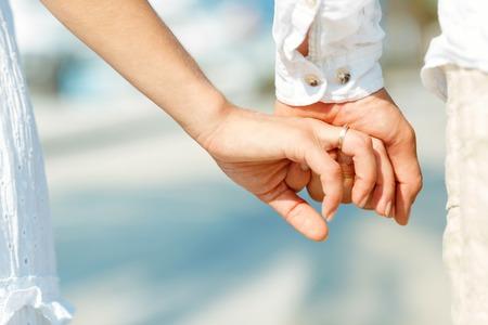 Concetto tiro di amicizia e di amore dell'uomo e della donna: due mani sopra lungomare