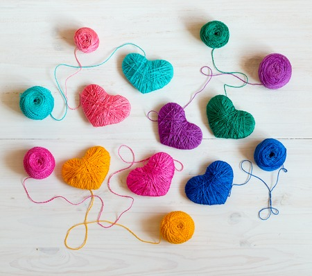 Multicolored Hearts with a balls of thread on white wooden background. Image of Valentines day