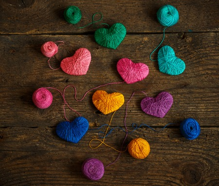 descriptive colours: Multicolored Hearts with a balls of thread on old shabby wooden background. Image of Valentines day Stock Photo