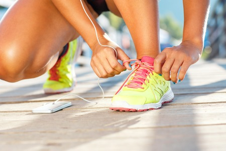 summer sport: Running shoes - woman tying shoe laces. Closeup of female sport fitness runner getting ready for jogging outdoors on waterfront in late summer or fall
