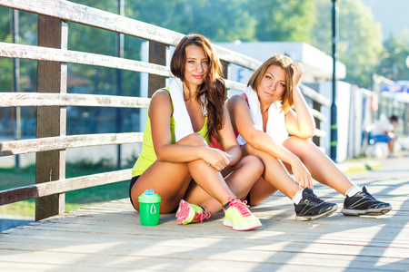 people street: Two cute girls have a rest after exercising outdoors Stock Photo
