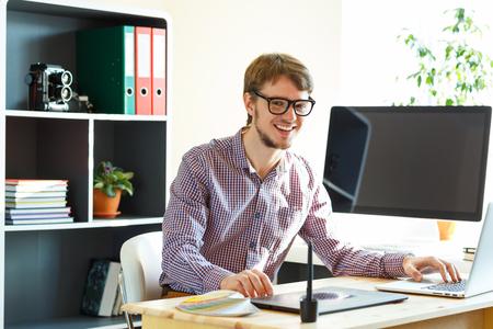 competencias laborales: Artista joven feliz dibujar algo en la tableta gráfica en la oficina en casa Foto de archivo