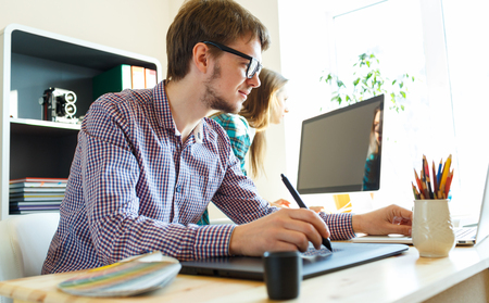 telecommuting: Successful young woman and man working from home - modern business concept Stock Photo