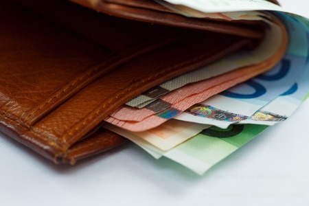 capitalization: Brown leather wallet with money euro inside it