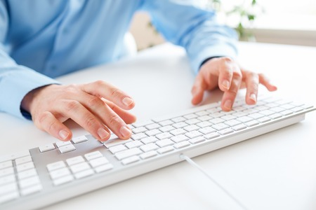 press button: Male hands or men office worker typing on the keyboard Stock Photo