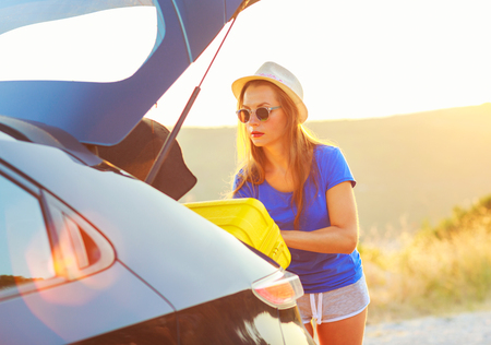 holiday trip: Young woman loading luggage into the back of car parked alongside the road