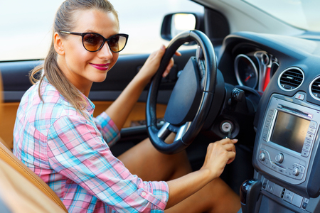 rental: Young beautiful woman sitting in a convertible and is going to start the engine - the concept of buying a used car or a rental car Stock Photo