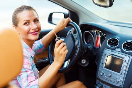 Vrouw zitten in een cabriolet en gaat naar de motor te starten - het concept van het kopen van een gebruikte auto of een huurauto Stockfoto